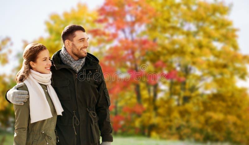Pares sonrientes que abrazan en parque del oto?o fotografía de archivo libre de regalías