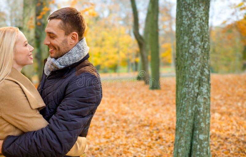Pares sonrientes que abrazan en parque del oto?o fotografía de archivo