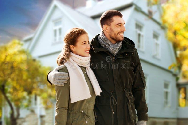 Pares sonrientes que abrazan sobre casa en otoño fotografía de archivo