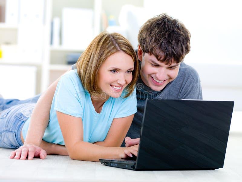 Pares sonrientes que miran la computadora portátil imagenes de archivo