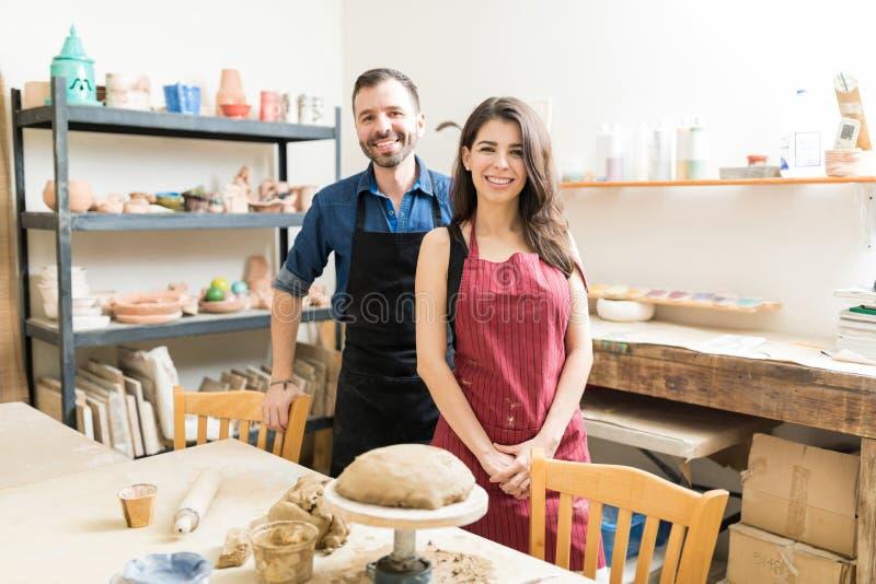 Pares sonrientes que pasan tiempo en el taller de la cerámica fotos de archivo
