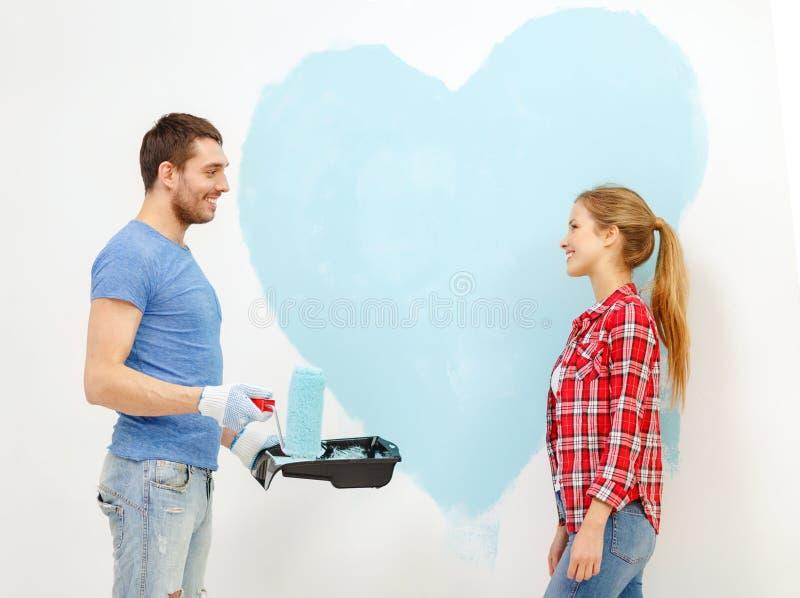 Pares sonrientes que pintan el corazón grande en la pared fotografía de archivo libre de regalías
