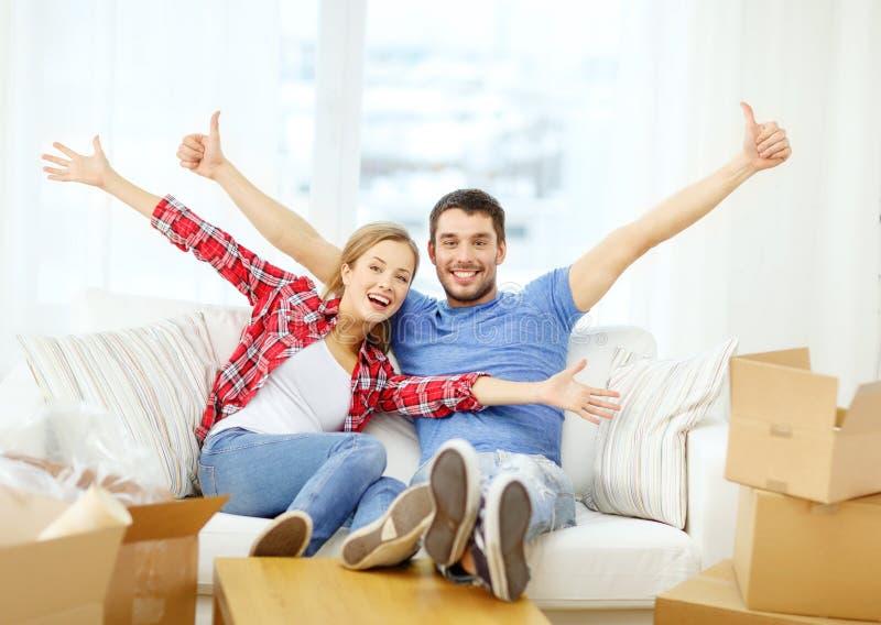 Pares sonrientes que se relajan en el sofá en nuevo hogar foto de archivo