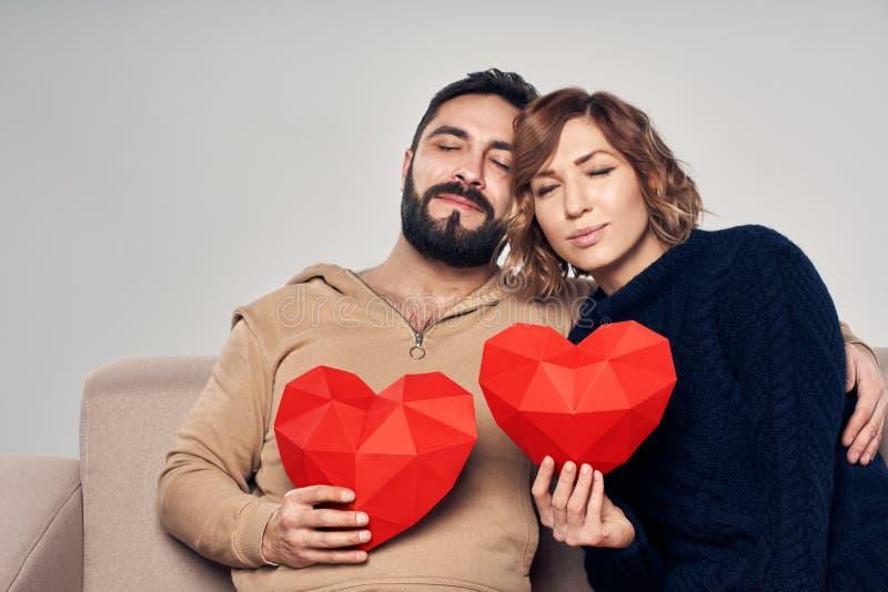 Pares sonrientes que se sientan en el sofá que lleva a cabo forma del corazón imágenes de archivo libres de regalías