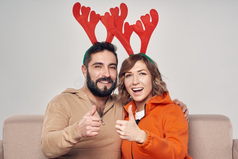 Pares sonrientes que se sientan en los trajes de los ciervos de la Navidad del sofá que llevan foto de archivo libre de regalías