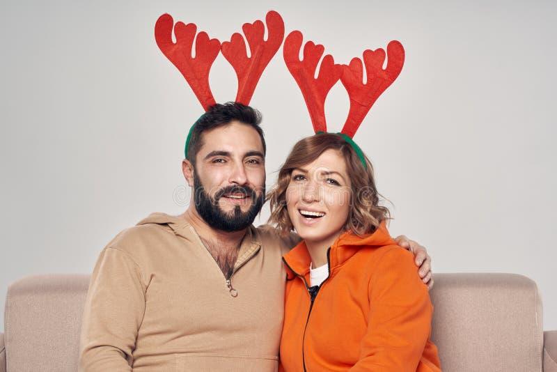 Pares sonrientes que se sientan en los trajes de los ciervos de la Navidad del sofá que llevan foto de archivo