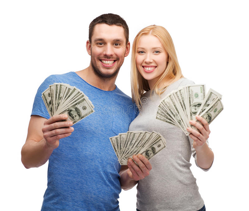 Pares sonrientes que sostienen el dinero del efectivo del dólar fotos de archivo