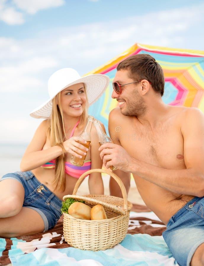 Pares sonrientes que tienen comida campestre en la playa imagen de archivo