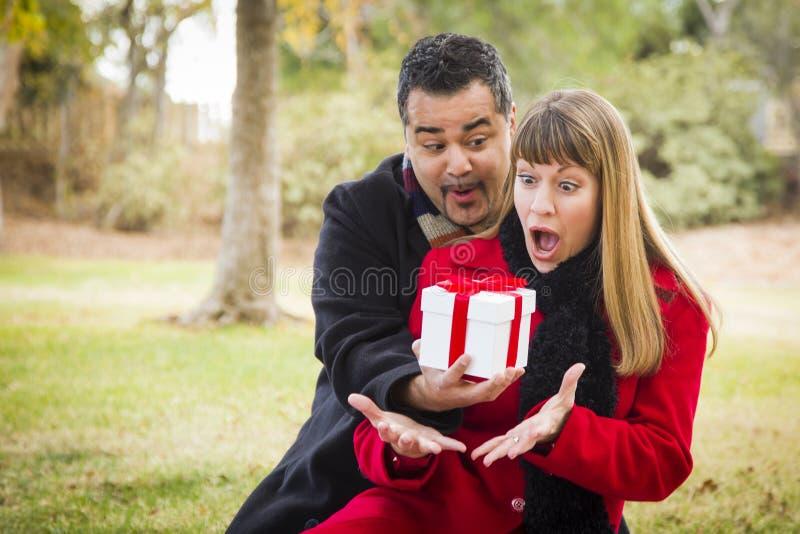 Pares sorprendidos de la raza mixta que dan los regalos fotos de archivo libres de regalías
