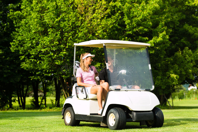 Pares sportive novos com carro de golfe em um curso imagens de stock