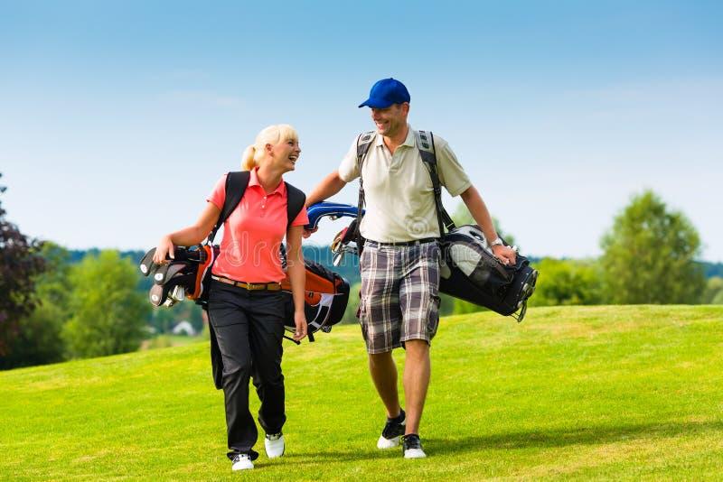 Pares sportive novos que jogam o golfe em um curso foto de stock