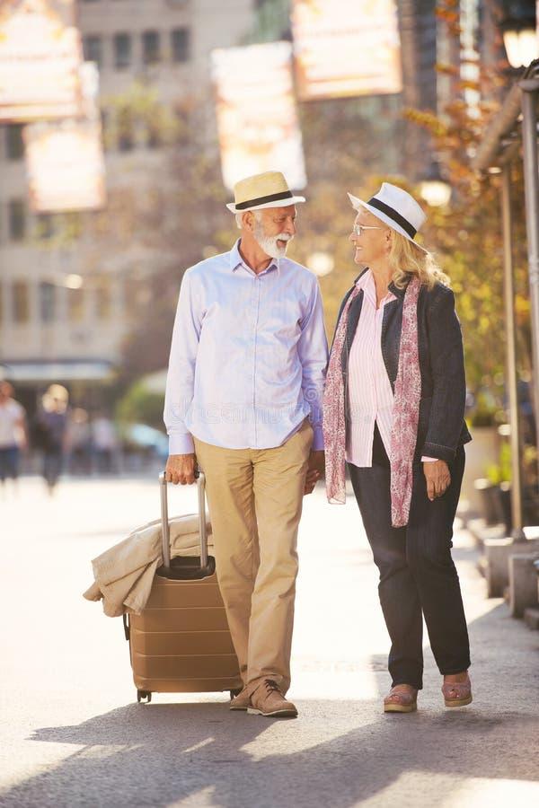 Pares superiores alegres felizes de turistas com o guia do mapa e da cidade que anda na rua foto de stock