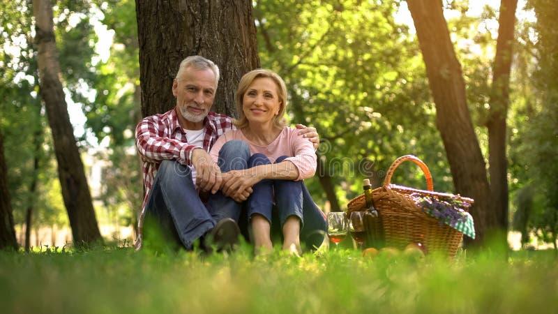 Pares superiores alegres que sentam-se na grama e que apreciam a data romântica, piquenique no parque imagens de stock