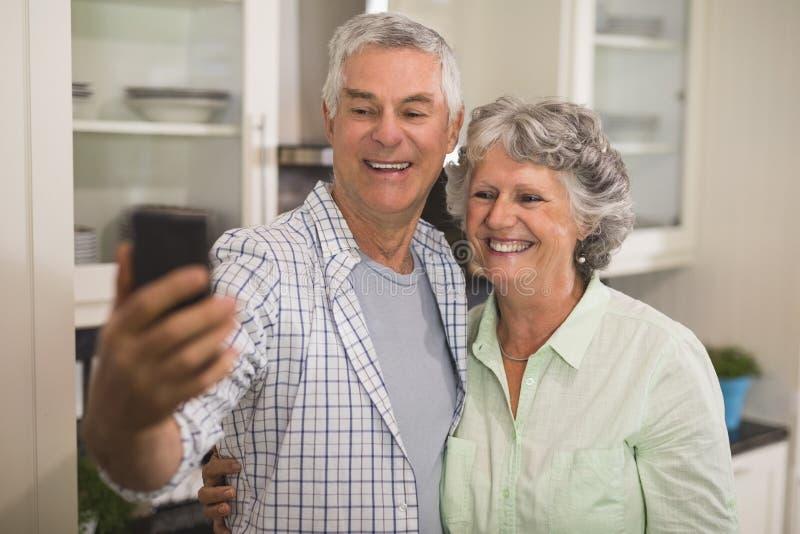 Pares superiores alegres que tomam o selfie na cozinha fotografia de stock royalty free