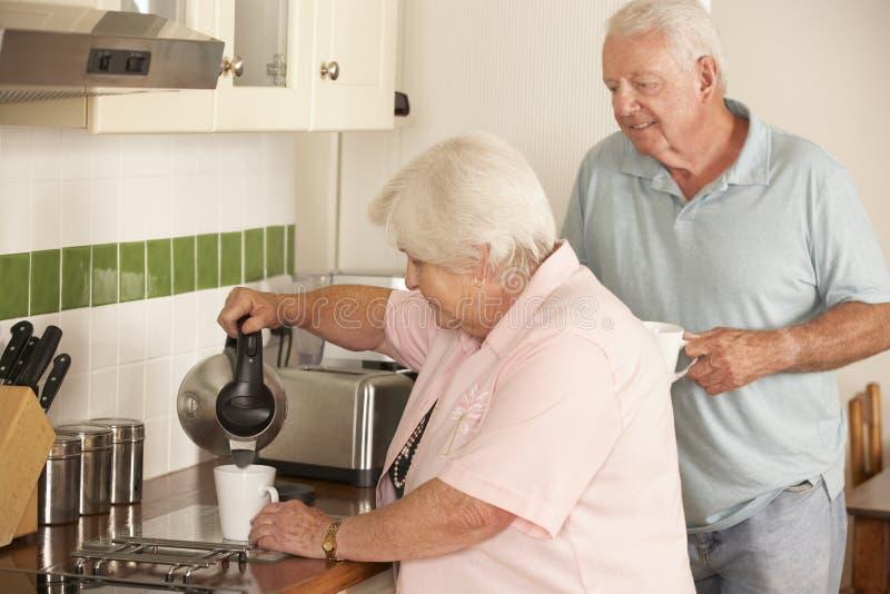 Pares superiores aposentados na cozinha que faz a bebida quente junto imagens de stock royalty free