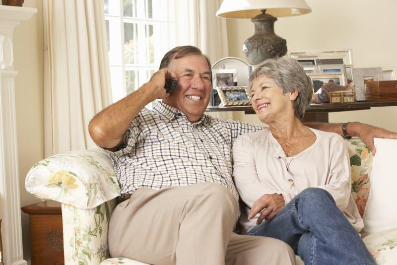 Pares superiores aposentados que sentam-se na casa de Sofa Talking On Phone At junto fotos de stock royalty free
