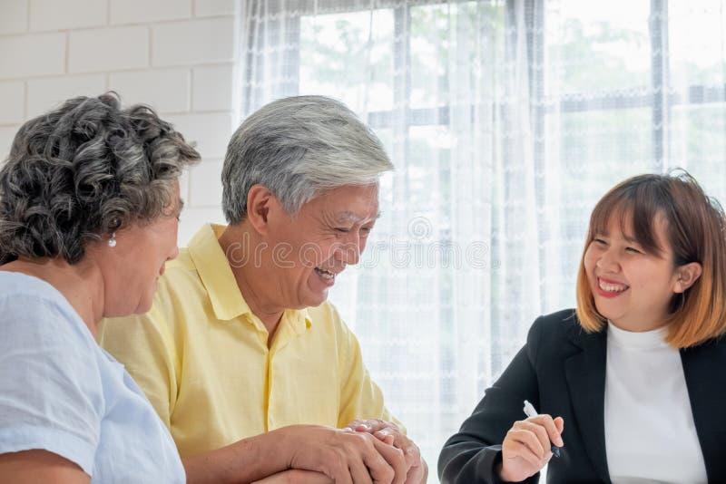 Pares superiores asiáticos com o conselheiro financeiro sobre o documento do imposto e da aposentadoria em casa conceito feliz d imagem de stock