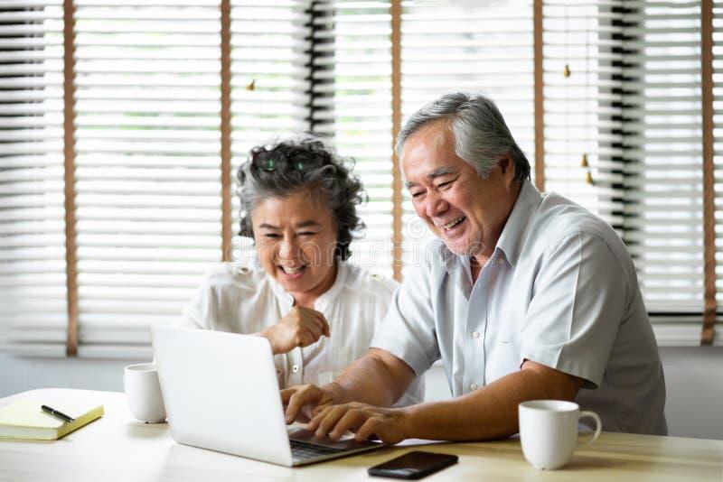 Pares superiores asiáticos de relaxamento que têm o divertimento com laptop imagens de stock royalty free
