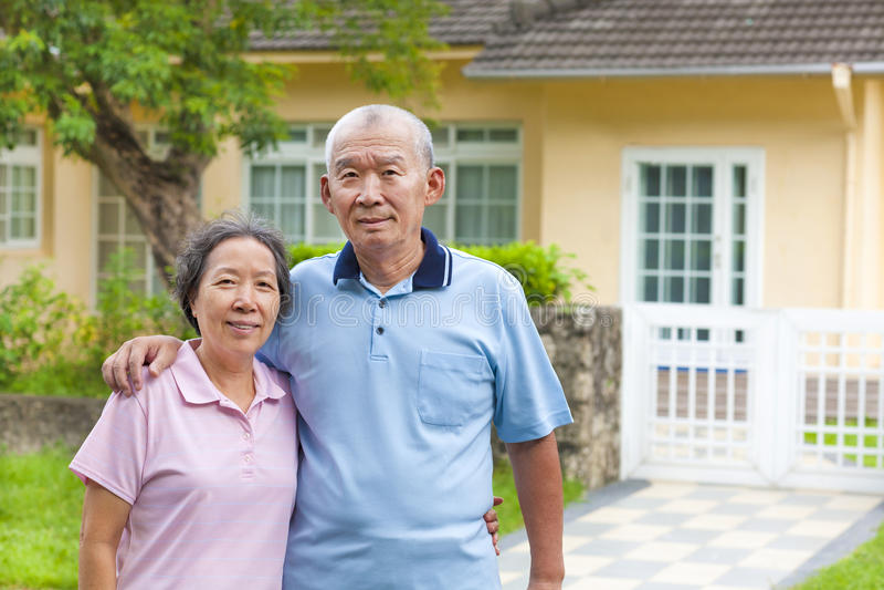 Pares superiores asiáticos felizes que estão na frente de uma casa foto de stock