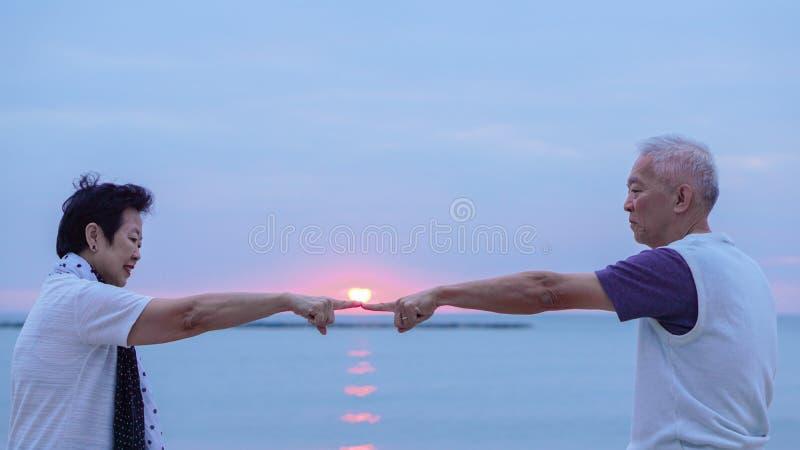Pares superiores asiáticos junto na praia do nascer do sol Ano novo, conceito novo da definição foto de stock royalty free