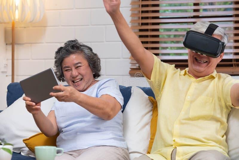 Pares superiores asiáticos para jogar junto vidros realtiy virtuais auriculares e o vídeo de observação do vr da tabuleta e para  imagem de stock royalty free