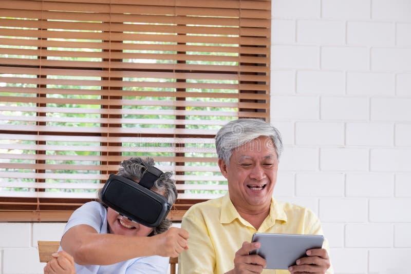 Pares superiores asiáticos para jogar junto vidros realtiy virtuais auriculares e o vídeo de observação do vr da tabuleta e para  imagens de stock
