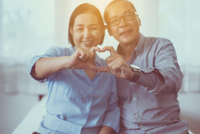 Pares superiores asiáticos que mostram a forma do coração das mãos junto, feliz felizes e sorrindo, pensamento do positivo foto de stock
