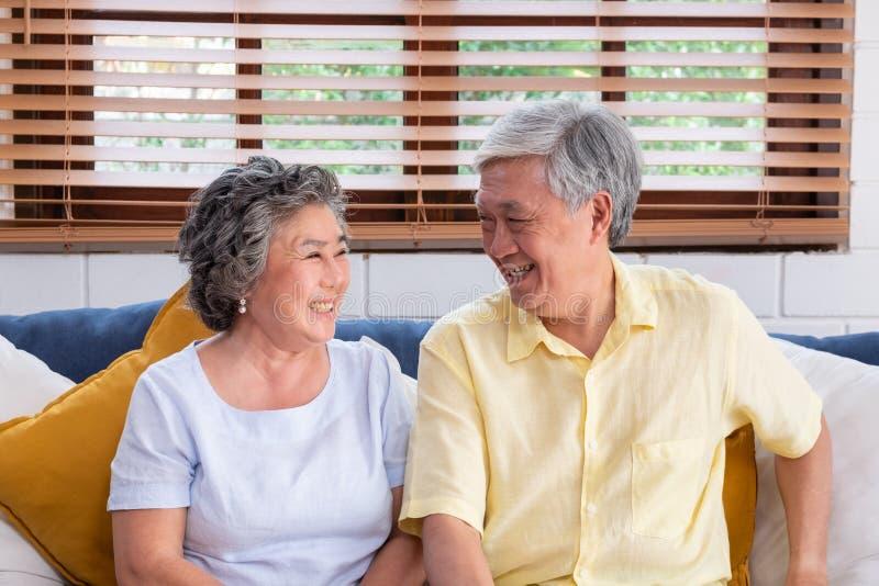 Pares superiores asiáticos que sentam-se e que abraçam no sofá na sala de visitas com amor envelhecendo em casa o conceito imagem de stock royalty free