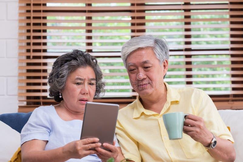 Pares superiores asiáticos usando o cálculo da tabela e para beber o café que senta-se no sofá na sala de visitas em casa superio foto de stock royalty free
