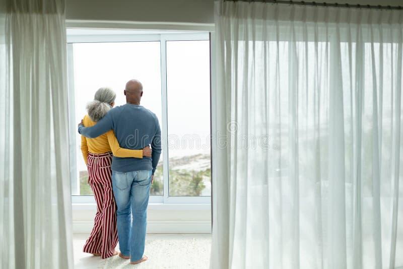 Pares superiores ativos com o braço em torno de estar perto da janela em casa imagem de stock royalty free