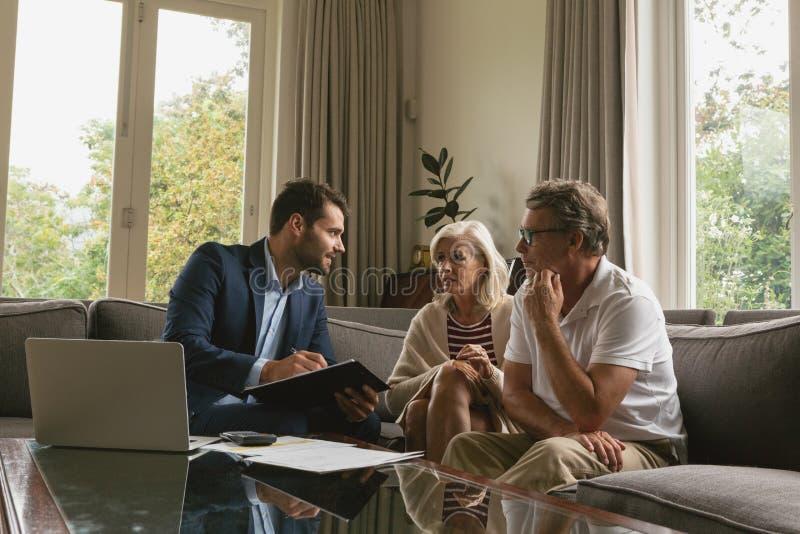 Pares superiores ativos que discutem com o mediador imobiliário sobre documentos na sala de visitas fotos de stock royalty free