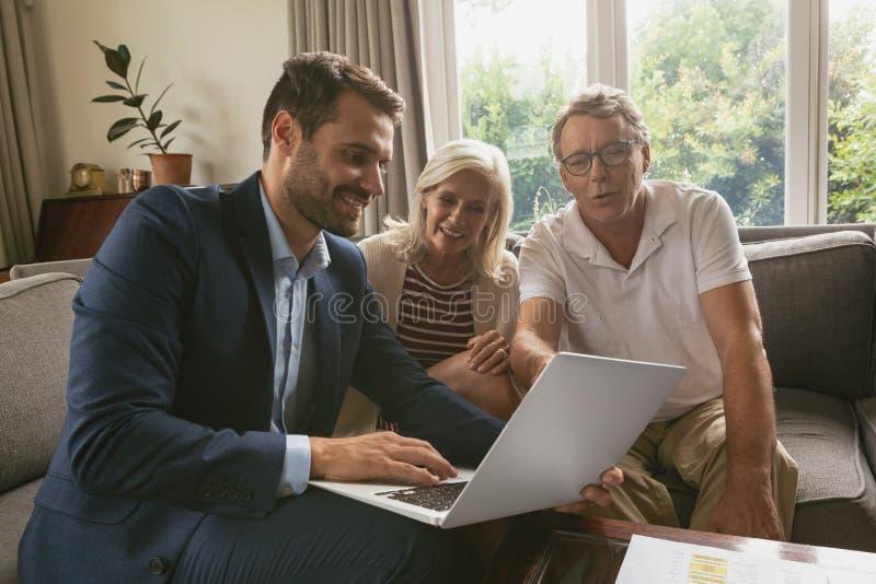 Pares superiores ativos que discutem com o mediador imobiliário sobre o portátil na sala de visitas imagens de stock royalty free