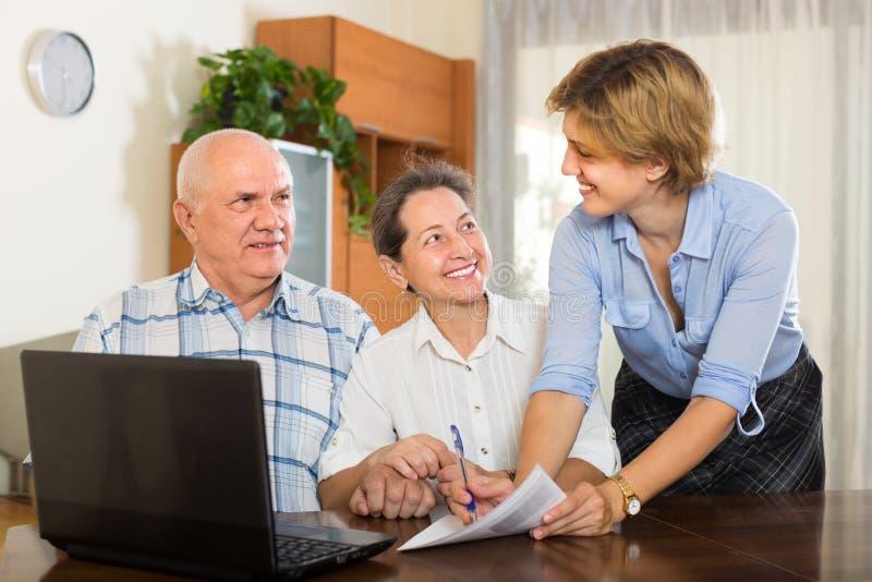 Pares superiores com assistente social em casa fotos de stock royalty free