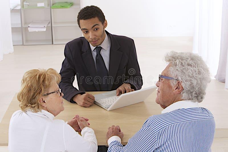 Pares superiores com consultante financeiro imagens de stock