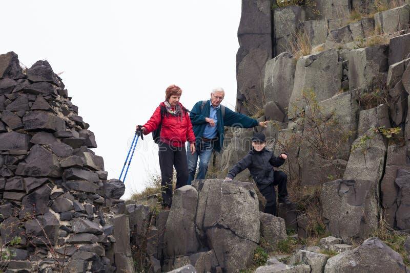Pares superiores com a criança que trekking na rocha fotos de stock royalty free