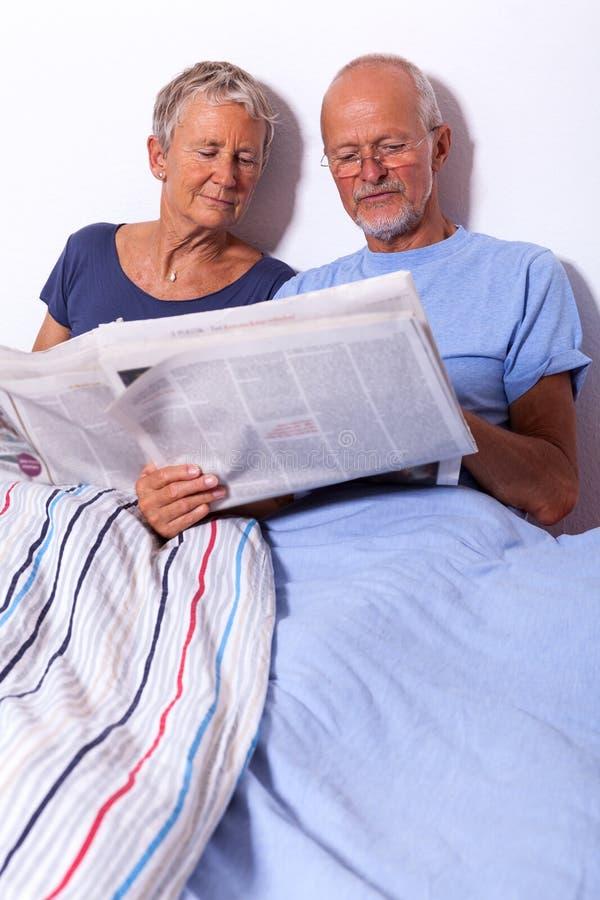 Pares superiores com tabuleta e jornal na cama imagens de stock royalty free