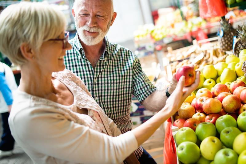 Pares superiores da família que escolhem bio frutas e legumes do alimento no mercado durante a compra semanal fotografia de stock