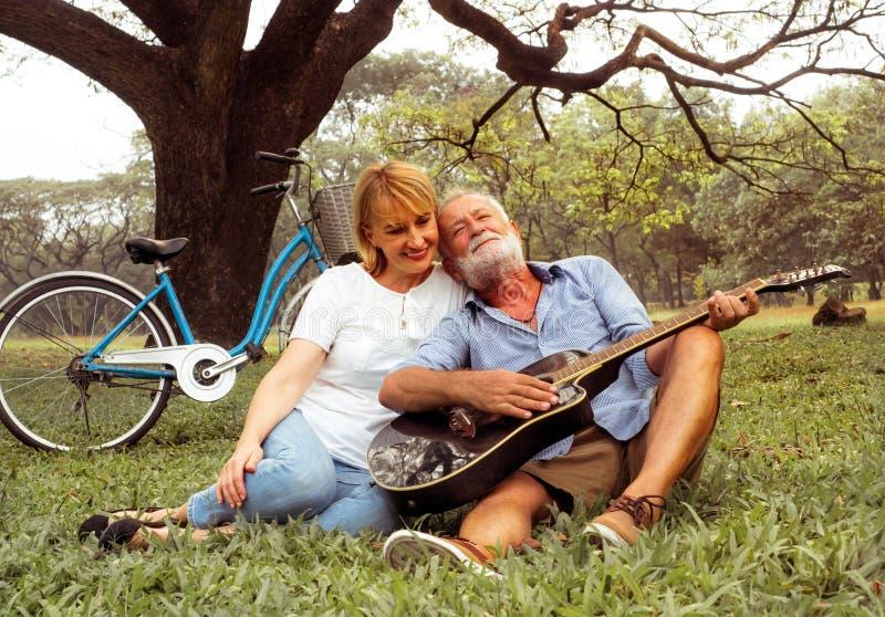 Pares superiores de amor felizes que passam o dia no campo e que têm o divertimento conceito sobre a antiguidade e os povos fotografia de stock royalty free