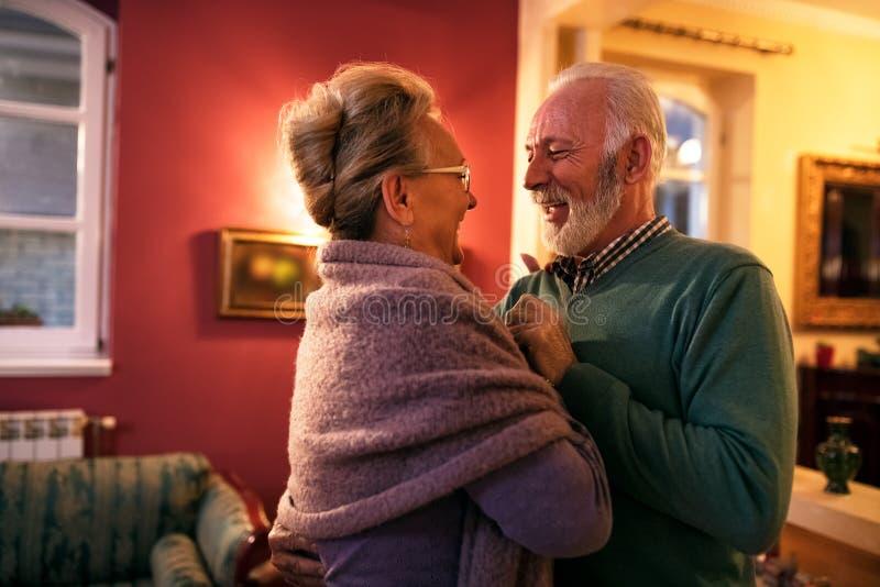 Pares superiores de sorriso bonitos no amor que dança em casa imagem de stock royalty free