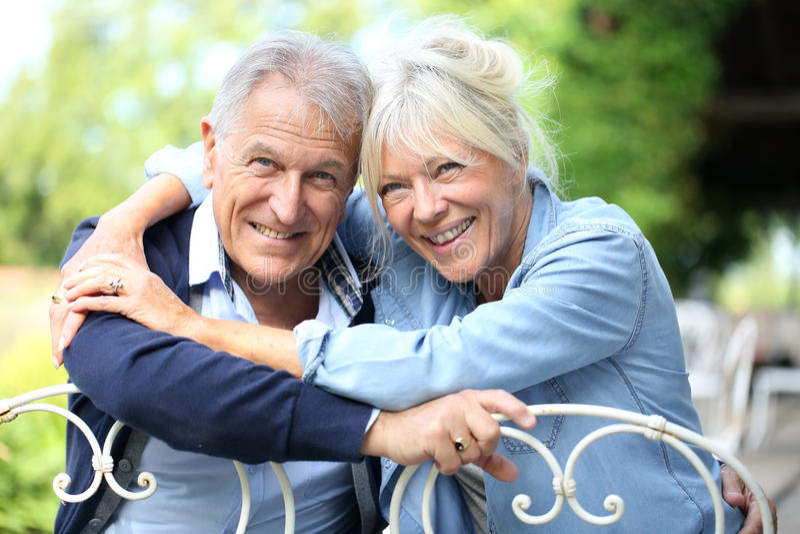 Pares superiores de sorriso felizes no jardim imagem de stock