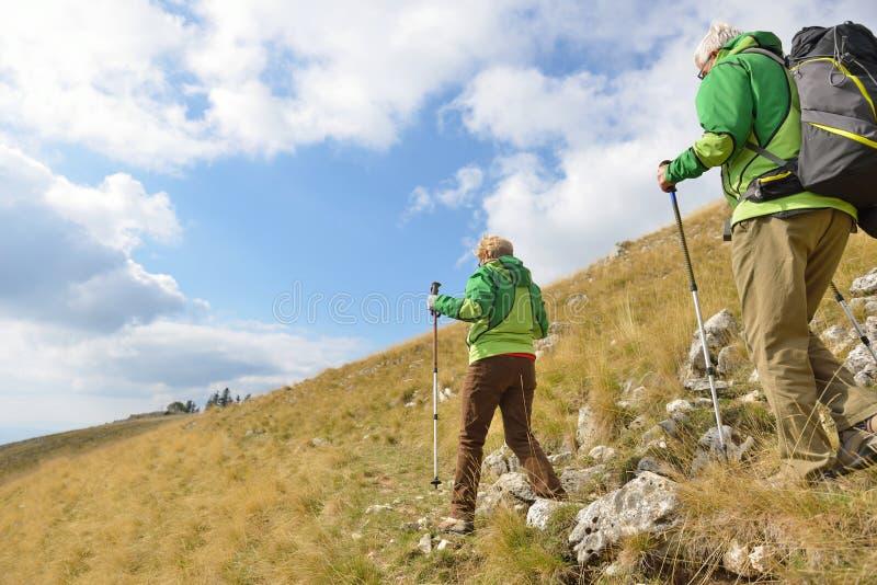Pares superiores do turista que caminham nas montanhas bonitas imagem de stock royalty free