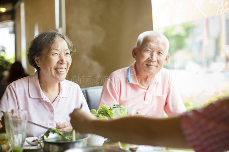 Pares superiores e família que comem potenciômetros quentes imagens de stock royalty free