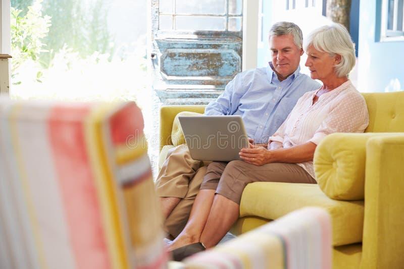 Pares superiores em casa na sala de estar usando o laptop foto de stock
