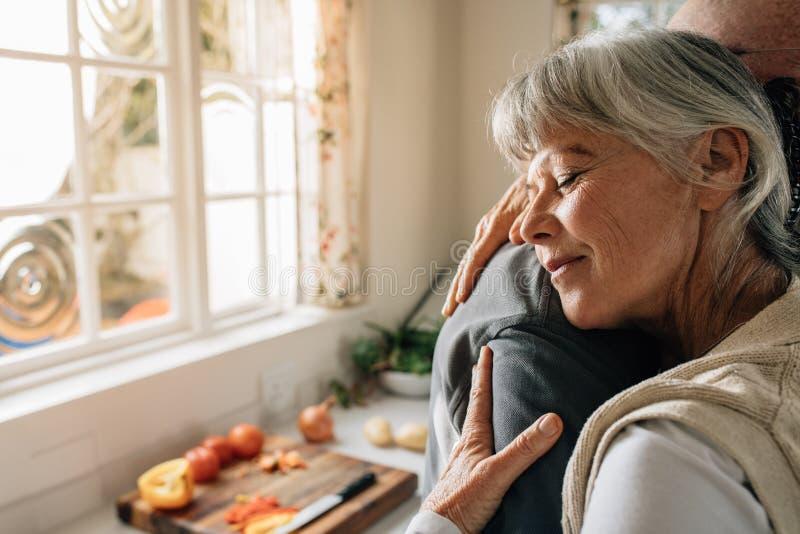 Pares superiores em casa que abraçam-se que está na cozinha Mulher superior que dá um abraço morno a seu marido na expressão dela fotografia de stock royalty free