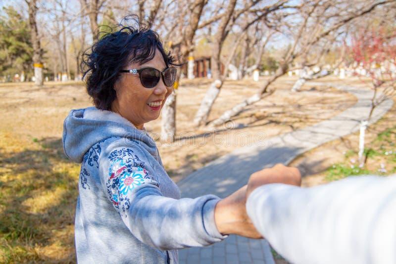 Pares superiores em conjunto, posição da mulher e riso no parque na queda fotografia de stock