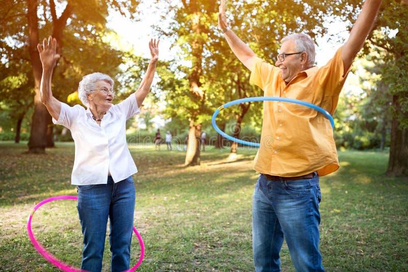 Pares superiores engraçados felizes que jogam o hulahop no parque fotografia de stock royalty free