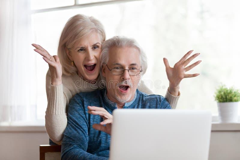 Pares superiores entusiasmado que olham o portátil surpreendido pela boa notícia imagens de stock royalty free