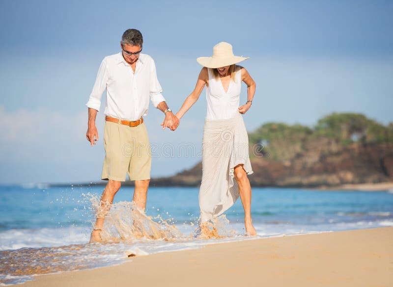 Pares superiores felizes na praia. Aposentadoria Res tropical luxuoso foto de stock