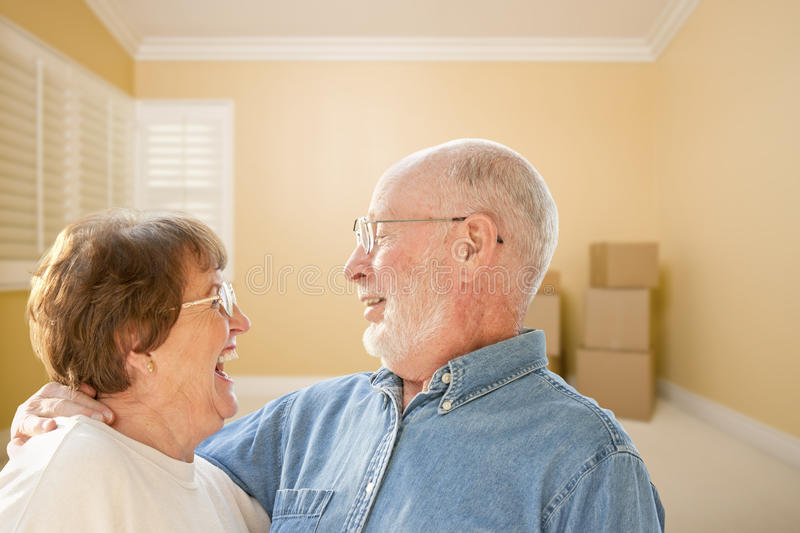 Pares superiores felizes na sala com as caixas moventes no assoalho imagens de stock