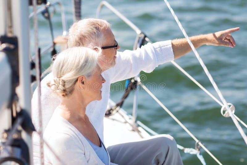 Pares superiores felizes no barco ou no iate de vela no mar fotos de stock